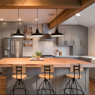 ワシントンD.C.の大きいトランジショナルスタイルのおしゃれなキッチン (エプロンフロントシンク、シェーカースタイル扉のキャビネット、グレーのキャビネット、木材カウンター、白いキッチンパネル、サブウェイタイルのキッチンパネル、シルバーの調理設備、無垢フローリング) の写真