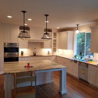 This is an example of a large traditional galley eat-in kitchen in Other with an undermount sink, louvered cabinets, white cabinets, granite benchtops, white splashback, window splashback, stainless steel appliances, light hardwood floors, with island and grey benchtop.