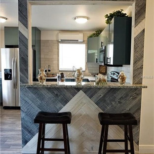 Photo of a mid-sized modern l-shaped eat-in kitchen in Tampa with a double-bowl sink, flat-panel cabinets, turquoise cabinets, granite benchtops, grey splashback, ceramic splashback, stainless steel appliances, ceramic floors, a peninsula, grey floor and grey benchtop.