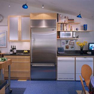 Modelo de cocina comedor actual con armarios tipo vitrina, puertas de armario de madera clara y electrodomésticos de acero inoxidable