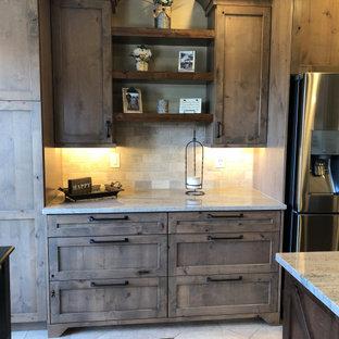 デンバーの大きいラスティックスタイルのおしゃれなキッチン (アンダーカウンターシンク、シェーカースタイル扉のキャビネット、ヴィンテージ仕上げキャビネット、御影石カウンター、ベージュキッチンパネル、トラバーチンの床、シルバーの調理設備の、トラバーチンの床、ベージュの床、茶色いキッチンカウンター) の写真