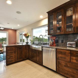 オースティンの中サイズのサンタフェスタイルのおしゃれなキッチン (エプロンフロントシンク、シェーカースタイル扉のキャビネット、濃色木目調キャビネット、御影石カウンター、グレーのキッチンパネル、シルバーの調理設備の、淡色無垢フローリング) の写真