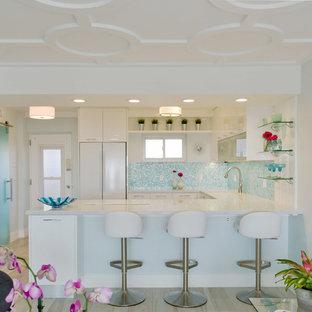 Exempel på ett mellanstort modernt kök, med en undermonterad diskho, släta luckor, vita skåp, bänkskiva i kvarts, blått stänkskydd, stänkskydd i glaskakel, vita vitvaror, klinkergolv i keramik och en halv köksö