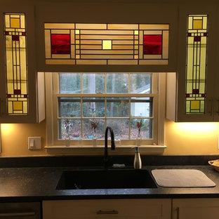 アトランタの中サイズのトラディショナルスタイルのおしゃれなキッチン (アンダーカウンターシンク、落し込みパネル扉のキャビネット、白いキャビネット、人工大理石カウンター、マルチカラーのキッチンパネル、ガラスタイルのキッチンパネル、シルバーの調理設備の、無垢フローリング、アイランドなし、茶色い床、黒いキッチンカウンター) の写真
