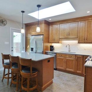 他の地域のトランジショナルスタイルのおしゃれなキッチン (アンダーカウンターシンク、落し込みパネル扉のキャビネット、中間色木目調キャビネット、クオーツストーンカウンター、白いキッチンパネル、サブウェイタイルのキッチンパネル、シルバーの調理設備の、磁器タイルの床) の写真