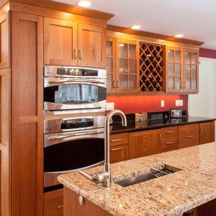ボストンのトラディショナルスタイルのおしゃれなキッチン (アンダーカウンターシンク、落し込みパネル扉のキャビネット、中間色木目調キャビネット、御影石カウンター、赤いキッチンパネル、シルバーの調理設備の) の写真