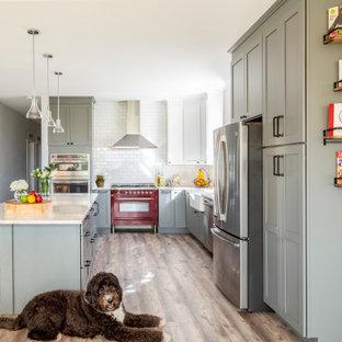 デンバーのトランジショナルスタイルのおしゃれなキッチン (エプロンフロントシンク、シェーカースタイル扉のキャビネット、グレーのキャビネット、白いキッチンパネル、サブウェイタイルのキッチンパネル、カラー調理設備、茶色い床、白いキッチンカウンター) の写真