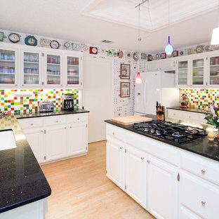 オースティンの中サイズのエクレクティックスタイルのおしゃれなキッチン (シングルシンク、レイズドパネル扉のキャビネット、白いキャビネット、御影石カウンター、マルチカラーのキッチンパネル、モザイクタイルのキッチンパネル、白い調理設備、竹フローリング、茶色い床、黒いキッチンカウンター) の写真