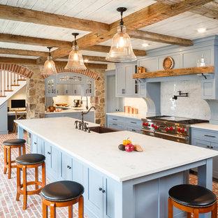 フィラデルフィアの広いカントリー風おしゃれなキッチン (エプロンフロントシンク、シェーカースタイル扉のキャビネット、青いキャビネット、シルバーの調理設備、レンガの床) の写真