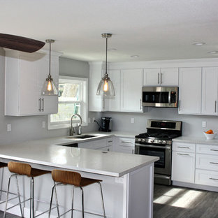 Photo of a mid-sized arts and crafts eat-in kitchen in Orange County with a drop-in sink, flat-panel cabinets, white cabinets, limestone benchtops, stainless steel appliances, ceramic floors and with island.