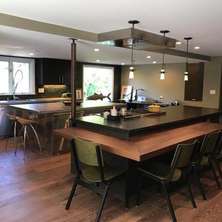 Inspiration for a large modern l-shaped eat-in kitchen in New York with an undermount sink, flat-panel cabinets, black cabinets, green splashback, subway tile splashback, stainless steel appliances, dark hardwood floors, multiple islands, brown floor and zinc benchtops.