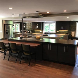 This is an example of a large modern l-shaped eat-in kitchen in New York with an undermount sink, flat-panel cabinets, black cabinets, green splashback, subway tile splashback, stainless steel appliances, dark hardwood floors, multiple islands, brown floor and zinc benchtops.