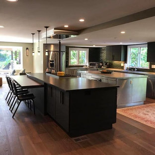Photo of a large modern l-shaped eat-in kitchen in New York with an undermount sink, flat-panel cabinets, black cabinets, green splashback, subway tile splashback, stainless steel appliances, dark hardwood floors, multiple islands, brown floor and zinc benchtops.