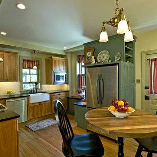 Bild på ett mellanstort lantligt kök, med en rustik diskho, släta luckor, skåp i mellenmörkt trä, bänkskiva i täljsten, vitt stänkskydd, stänkskydd i metallkakel, rostfria vitvaror och ljust trägolv