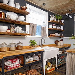 Inspiration för ett avskilt, mellanstort rustikt parallellkök, med en rustik diskho, luckor med glaspanel, svarta skåp, träbänkskiva, rostfria vitvaror, mellanmörkt trägolv och en köksö