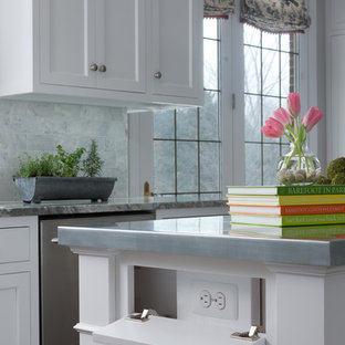 Design ideas for a mid-sized traditional u-shaped eat-in kitchen in Detroit with an undermount sink, shaker cabinets, white cabinets, zinc benchtops, grey splashback, marble splashback, stainless steel appliances, medium hardwood floors, with island and brown floor.