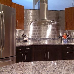 タンパの中くらいのインダストリアルスタイルのおしゃれなキッチン (フラットパネル扉のキャビネット、中間色木目調キャビネット、御影石カウンター、メタリックのキッチンパネル、メタルタイルのキッチンパネル、シルバーの調理設備、アンダーカウンターシンク) の写真