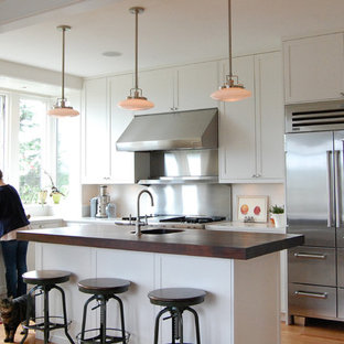 Inspiration for a timeless l-shaped kitchen remodel in Seattle with a farmhouse sink, wood countertops and stainless steel appliances