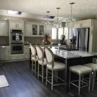 Inspiration för stora klassiska svart kök, med en undermonterad diskho, luckor med infälld panel, vita skåp, granitbänkskiva, vitt stänkskydd, stänkskydd i keramik, rostfria vitvaror, laminatgolv, en köksö och grått golv