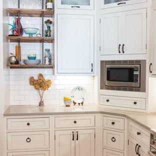 セントルイスの中くらいのカントリー風おしゃれなキッチン (エプロンフロントシンク、インセット扉のキャビネット、白いキャビネット、珪岩カウンター、白いキッチンパネル、サブウェイタイルのキッチンパネル、シルバーの調理設備、セラミックタイルの床) の写真