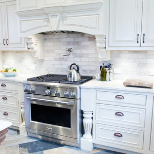 Design ideas for a mid-sized transitional l-shaped eat-in kitchen in New York with a farmhouse sink, beaded inset cabinets, beige cabinets, quartzite benchtops, grey splashback, porcelain splashback, stainless steel appliances, porcelain floors, with island and blue floor.