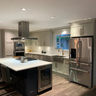 Large arts and crafts l-shaped open plan kitchen in Vancouver with a farmhouse sink, shaker cabinets, beige cabinets, quartz benchtops, white splashback, ceramic splashback, stainless steel appliances, laminate floors, with island, grey floor and white benchtop.