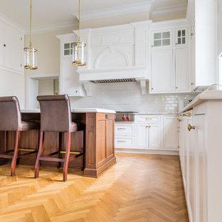 シカゴの広いモダンスタイルのおしゃれなキッチン (白いキャビネット、白いキッチンパネル、シルバーの調理設備、白いキッチンカウンター、アンダーカウンターシンク、サブウェイタイルのキッチンパネル、淡色無垢フローリング、黄色い床、クオーツストーンカウンター、シェーカースタイル扉のキャビネット) の写真