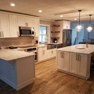 Inspiration for a large beach style single-wall eat-in kitchen in Other with a farmhouse sink, shaker cabinets, white cabinets, granite benchtops, grey splashback, ceramic splashback, stainless steel appliances, ceramic floors and with island.
