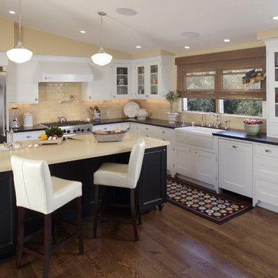Example of a classic l-shaped kitchen design in San Francisco with glass-front cabinets, stainless steel appliances, a farmhouse sink, white cabinets, granite countertops, beige backsplash and subway tile backsplash