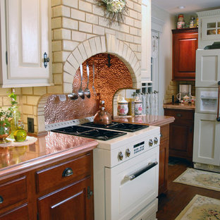 Mid-sized farmhouse enclosed kitchen inspiration - Example of a mid-sized cottage u-shaped dark wood floor enclosed kitchen design in Cincinnati with a single-bowl sink, medium tone wood cabinets, copper countertops, beige backsplash, subway tile backsplash, colored appliances and an island