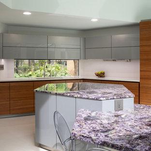 Mittelgroße Moderne Wohnküche mit Unterbauwaschbecken, flächenbündigen Schrankfronten, hellbraunen Holzschränken, Mineralwerkstoff-Arbeitsplatte, Küchengeräten aus Edelstahl, Porzellan-Bodenfliesen, Kücheninsel, weißem Boden und lila Arbeitsplatte in Houston