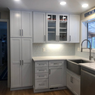 Inspiration for a mid-sized beach style u-shaped eat-in kitchen in Portland Maine with a farmhouse sink, shaker cabinets, white cabinets, soapstone benchtops, blue splashback, mosaic tile splashback, stainless steel appliances, medium hardwood floors, no island, multi-coloured floor and white benchtop.