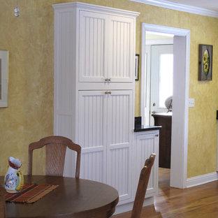 ミルウォーキーの中サイズのカントリー風おしゃれなキッチン (エプロンフロントシンク、インセット扉のキャビネット、白いキャビネット、御影石カウンター、黄色いキッチンパネル、白い調理設備、無垢フローリング) の写真