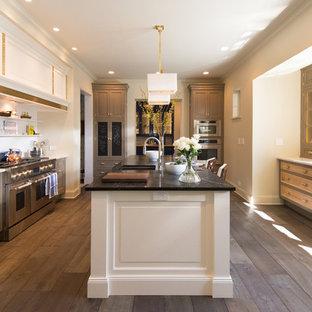 Cette image montre une grand cuisine ouverte parallèle traditionnelle avec un évier encastré, des portes de placard blanches, un plan de travail en onyx, une crédence blanche, une crédence en carrelage de pierre, un électroménager en acier inoxydable, un sol en bois brun, un îlot central, un sol marron et un placard avec porte à panneau surélevé.