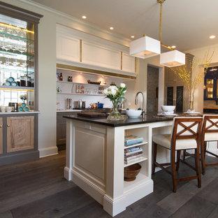 シカゴの広いトラディショナルスタイルのおしゃれなキッチン (アンダーカウンターシンク、落し込みパネル扉のキャビネット、白いキャビネット、オニキスカウンター、白いキッチンパネル、石スラブのキッチンパネル、シルバーの調理設備、無垢フローリング、茶色い床) の写真