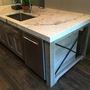 シカゴの中サイズのシャビーシック調のおしゃれなキッチン (アンダーカウンターシンク、フラットパネル扉のキャビネット、茶色いキャビネット、大理石カウンター、白いキッチンパネル、セラミックタイルのキッチンパネル、シルバーの調理設備の、濃色無垢フローリング、黒い床、白いキッチンカウンター) の写真