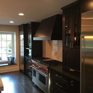 シカゴの中サイズのシャビーシック調のおしゃれなキッチン (アンダーカウンターシンク、フラットパネル扉のキャビネット、濃色木目調キャビネット、大理石カウンター、白いキッチンパネル、セラミックタイルのキッチンパネル、シルバーの調理設備の、濃色無垢フローリング、黒い床、白いキッチンカウンター) の写真