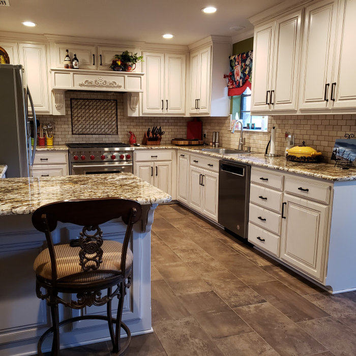 After, new kitchen with custom cabinets, custom paint details, new appliances, countertops, back splash, and lighting.