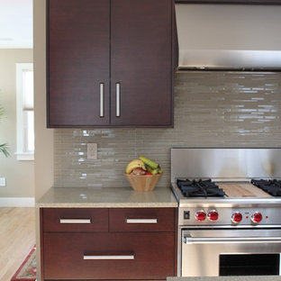 Example of a trendy kitchen design in Boston with stainless steel appliances, flat-panel cabinets, dark wood cabinets, matchstick tile backsplash and beige backsplash