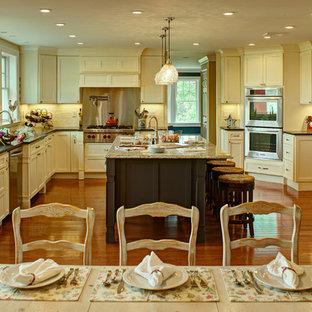 Immagine di una cucina tradizionale con ante gialle, paraspruzzi bianco e elettrodomestici in acciaio inossidabile
