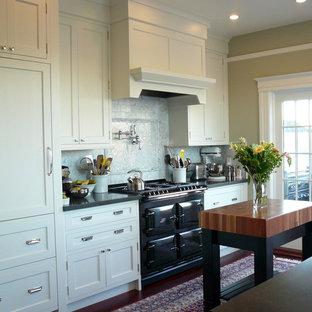Kitchen - traditional kitchen idea in San Francisco with shaker cabinets, white cabinets, white backsplash, stone tile backsplash, black appliances and quartz countertops