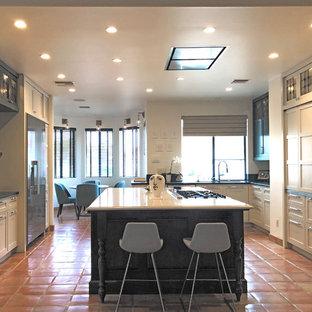 Exempel på ett mellanstort klassiskt gul gult kök, med en dubbel diskho, skåp i shakerstil, grå skåp, bänkskiva i kvarts, vitt stänkskydd, stänkskydd i sten, rostfria vitvaror, klinkergolv i terrakotta och en köksö