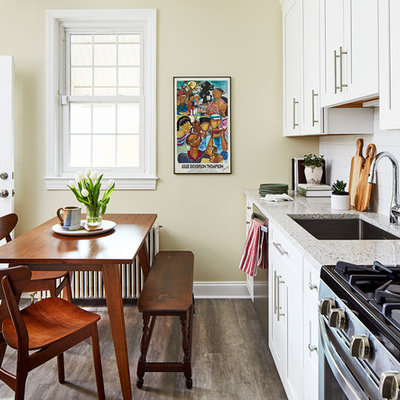 Inspiration for a timeless single-wall brown floor eat-in kitchen remodel in DC Metro with an undermount sink, shaker cabinets, white cabinets, white backsplash, subway tile backsplash, stainless steel appliances, no island and multicolored countertops