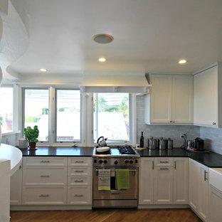 ロサンゼルスの中サイズのシャビーシック調のおしゃれなキッチン (エプロンフロントシンク、シェーカースタイル扉のキャビネット、白いキャビネット、グレーのキッチンパネル、石タイルのキッチンパネル、シルバーの調理設備、無垢フローリング、アイランドなし) の写真