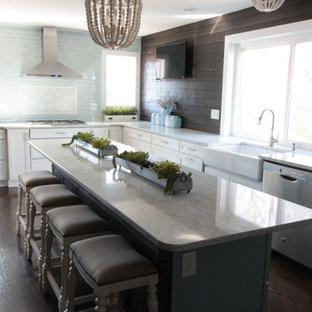 シンシナティの中サイズのカントリー風おしゃれなアイランドキッチン (エプロンフロントシンク、レイズドパネル扉のキャビネット、白いキャビネット、御影石カウンター、緑のキッチンパネル、セラミックタイルのキッチンパネル、シルバーの調理設備の、濃色無垢フローリング、茶色い床、緑のキッチンカウンター) の写真