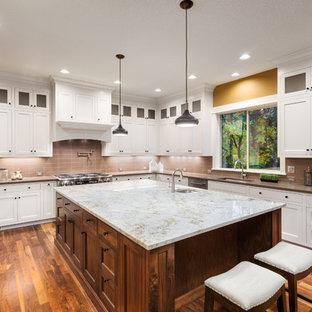 На фото: большая п-образная кухня в стиле модернизм с обеденным столом, врезной раковиной, фасадами в стиле шейкер, белыми фасадами, столешницей из кварцевого агломерата, розовым фартуком, фартуком из стеклянной плитки, техникой из нержавеющей стали, полом из бамбука, островом, коричневым полом и бежевой столешницей с