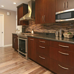 Contemporary kitchen inspiration - Trendy kitchen photo in San Francisco with stainless steel appliances, flat-panel cabinets, dark wood cabinets, matchstick tile backsplash and multicolored backsplash