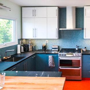 ロサンゼルスの中サイズのモダンスタイルのおしゃれなキッチン (フラットパネル扉のキャビネット、白いキャビネット、青いキッチンパネル、シルバーの調理設備の、リノリウムの床、オレンジの床、ドロップインシンク、御影石カウンター、モザイクタイルのキッチンパネル、黒いキッチンカウンター) の写真