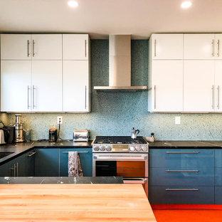 Bild på ett mellanstort funkis svart svart u-kök, med en undermonterad diskho, släta luckor, blått stänkskydd, rostfria vitvaror, linoleumgolv, en halv köksö, blå skåp, stänkskydd i mosaik, rött golv och granitbänkskiva