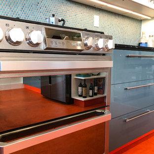 ロサンゼルスの中くらいのモダンスタイルのおしゃれなキッチン (フラットパネル扉のキャビネット、白いキャビネット、青いキッチンパネル、シルバーの調理設備、リノリウムの床、オレンジの床、ドロップインシンク、御影石カウンター、モザイクタイルのキッチンパネル、黒いキッチンカウンター) の写真